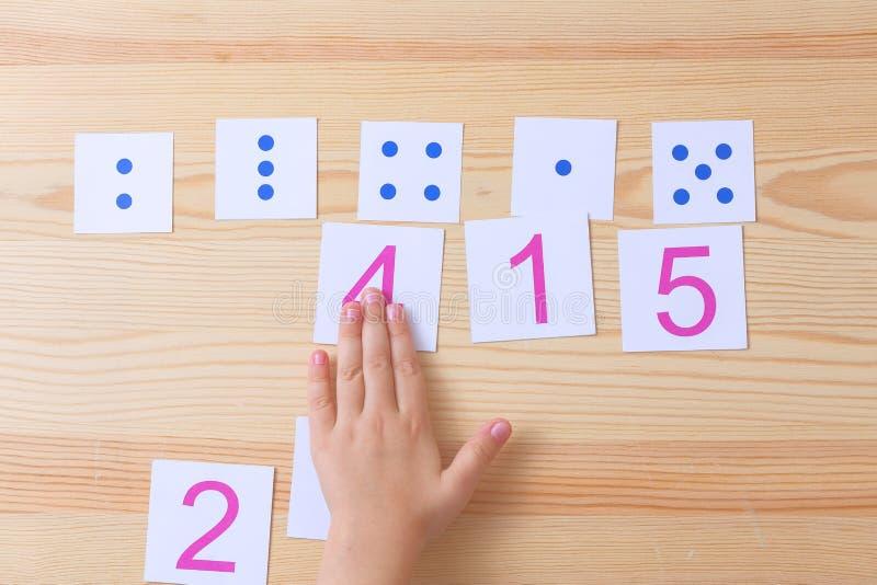 Il bambino sparge le carte con i numeri alle carte con i punti Lo studio sui numeri e sulla matematica fotografia stock libera da diritti