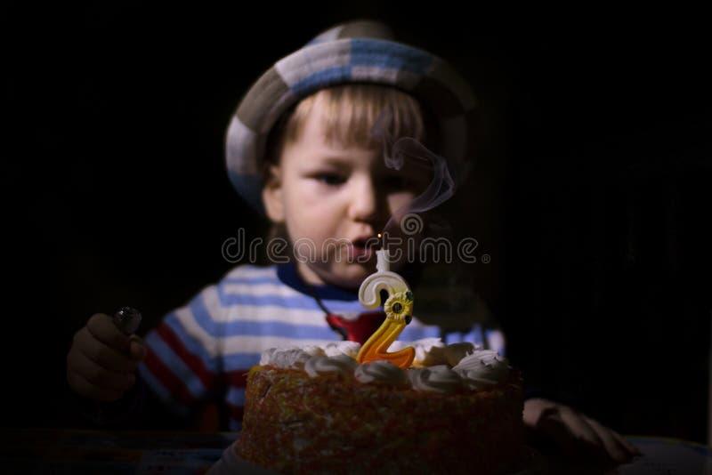 Il bambino spegne la candela sul compleanno del dolce immagini stock libere da diritti