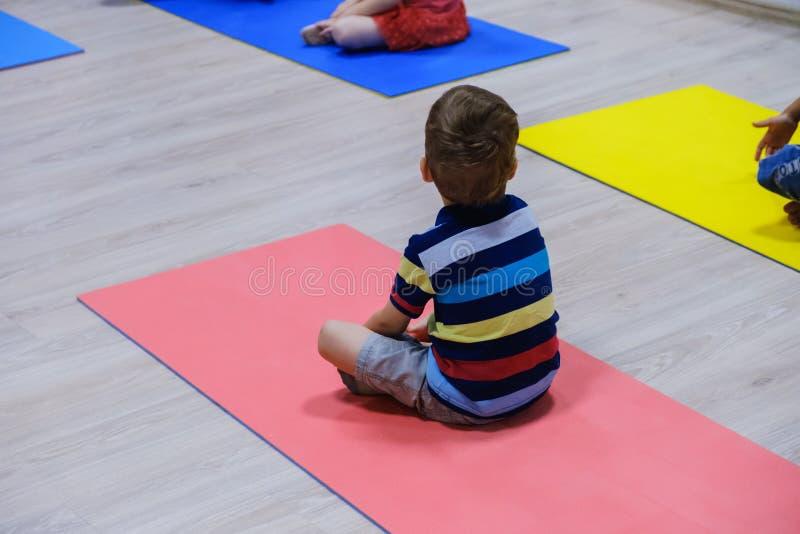 Il bambino sportivo sveglio che si esercita sulle stuoie in palestra, bambini di yoga mette in mostra il concetto della scuola fotografie stock libere da diritti