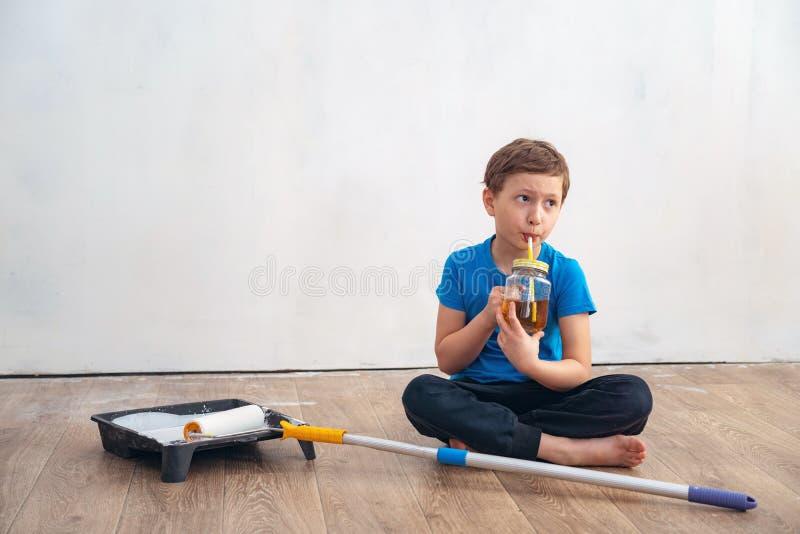Il bambino sta bevendo il tè durante la riparazione della parete il lavoro di finitura nei locali dell'artista dipinge le pareti  fotografia stock libera da diritti