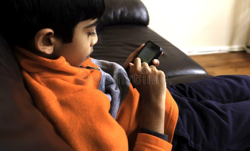 Il bambino sta esaminando il suo Smart Phone fotografie stock libere da diritti