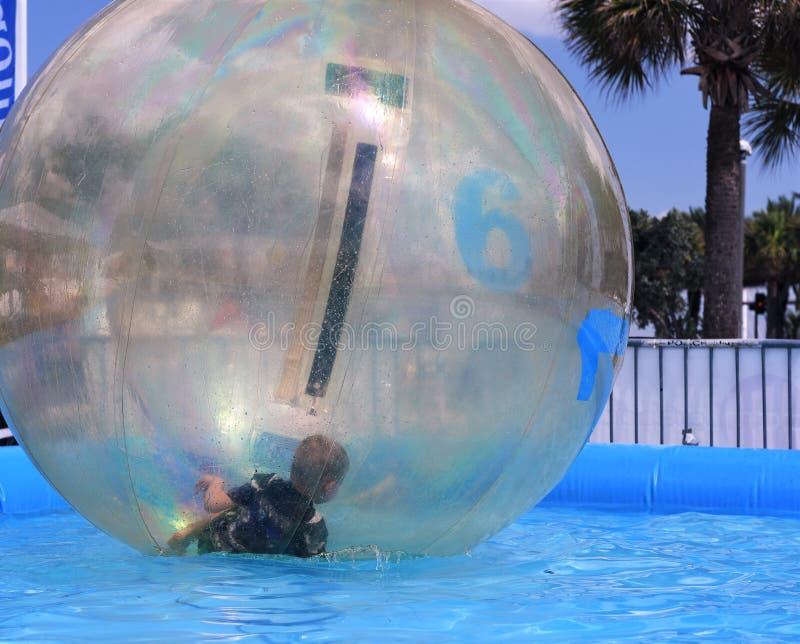 Il bambino sta giocando ed assomiglia all'intrappolato a dentro una bolla fotografia stock