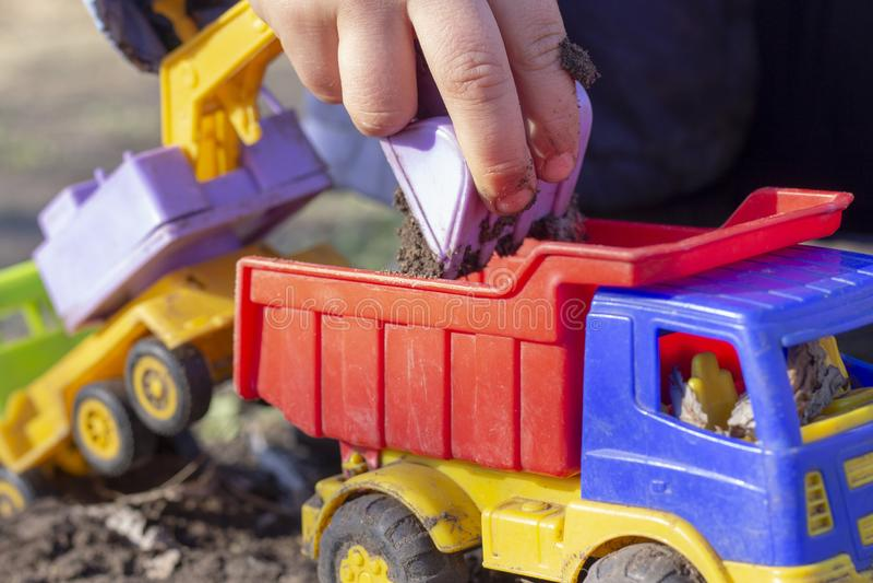Il bambino sta giocando nella via con la sabbia; carica la terra in un giocattolo dell'autocarro con cassone ribaltabile fotografia stock