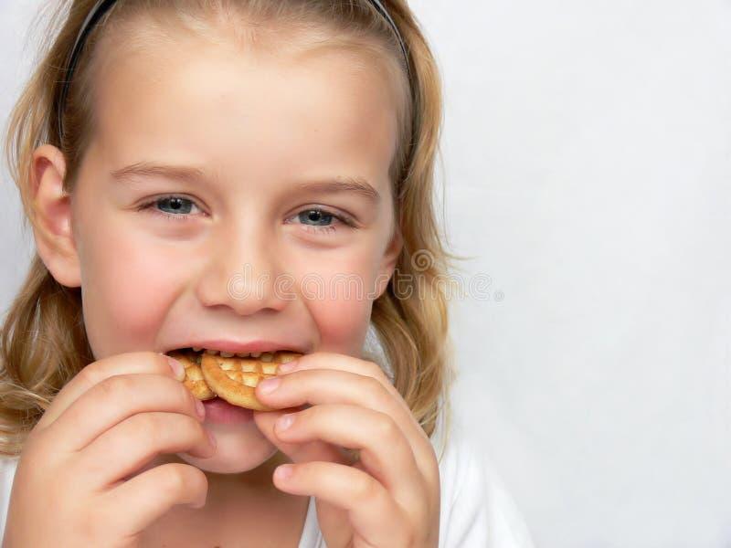 Il bambino sta mangiando i biscotti fotografie stock libere da diritti