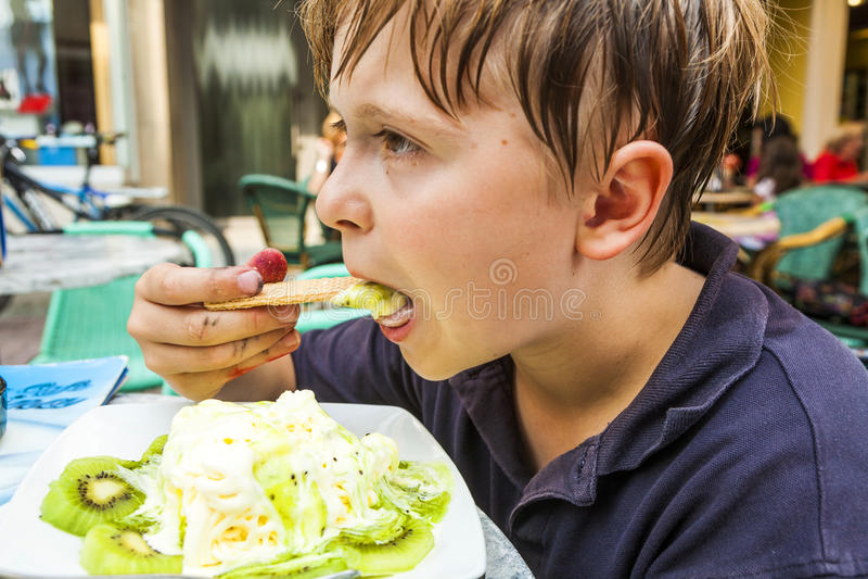 Il bambino sta mangiando il gelato ad una tavola all'aperto fotografia stock