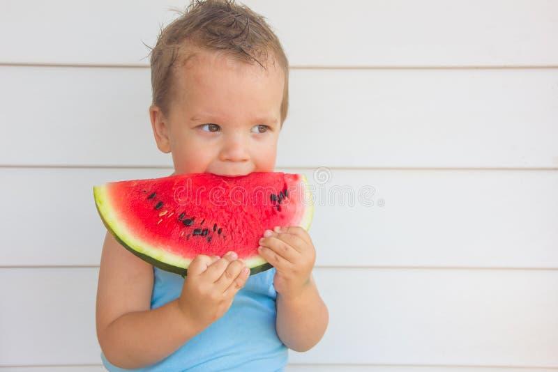Il bambino sta mangiando un'anguria immagine stock libera da diritti