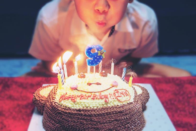 Il bambino sta soffiando felicemente le candele sulla sua torta di compleanno immagine stock libera da diritti