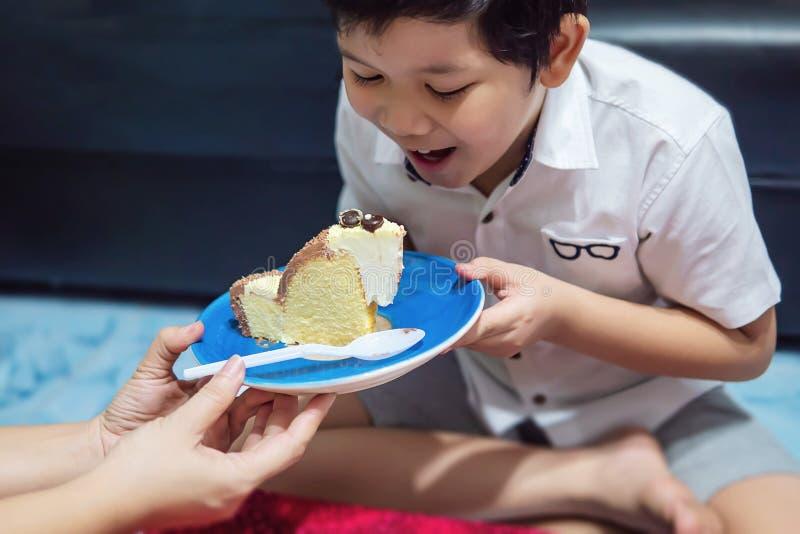 Il bambino sta soffiando felicemente le candele sulla sua torta di compleanno fotografia stock