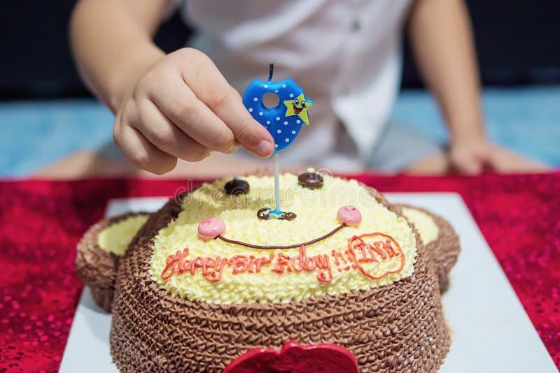 Il bambino sta soffiando felicemente le candele sulla sua torta di compleanno fotografia stock libera da diritti