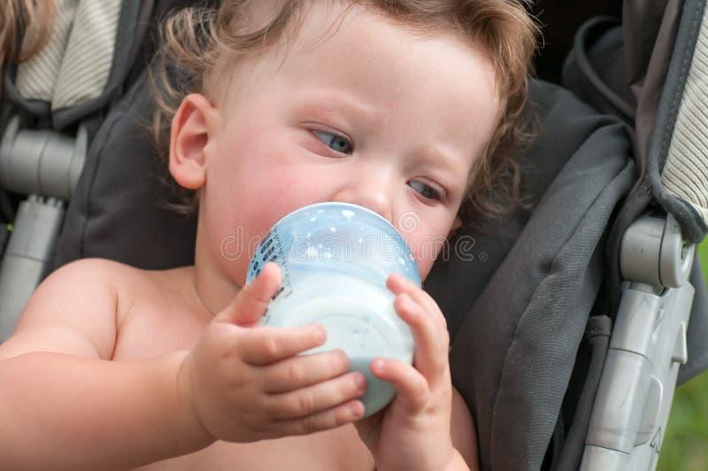 Il bambino succhia una bottiglia con latte fotografia stock libera da diritti