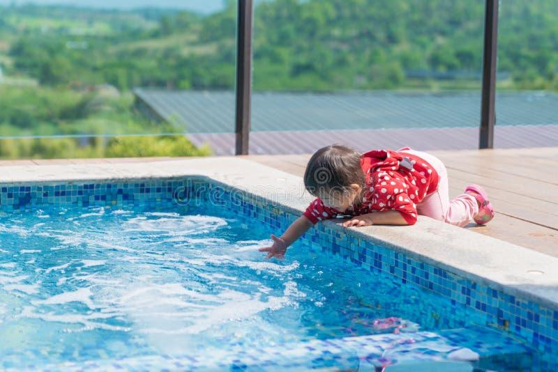 Il bambino sveglio asiatico della ragazza vuole giocare l'acqua nello stagno fotografia stock