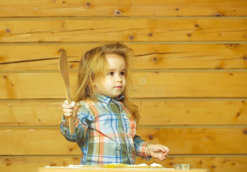 Il bambino sveglio che cucina con la pasta, farina tiene la pala di legno immagini stock