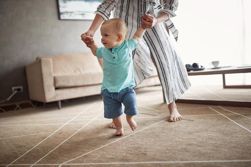 Il bambino sveglio che impara la camminata con la madre, bambino gode della prima s fotografia stock libera da diritti