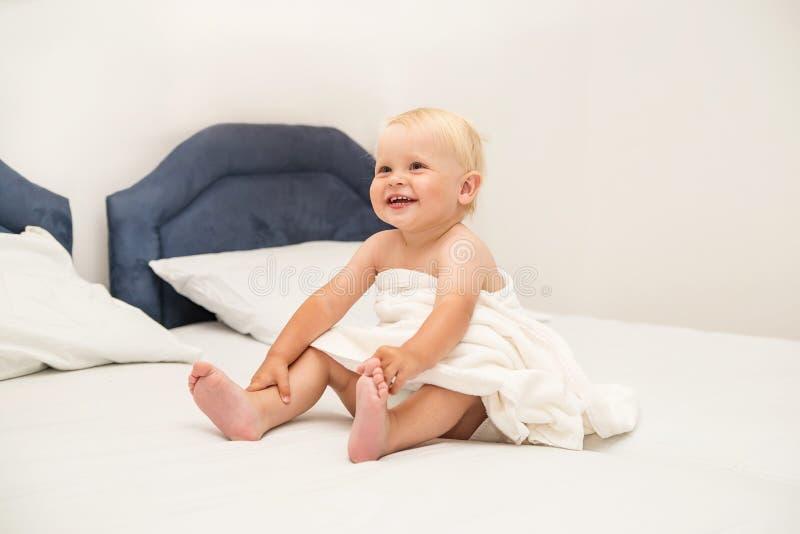 Il bambino sveglio che sorride sotto un asciugamano bianco e si siede sul letto fotografie stock libere da diritti