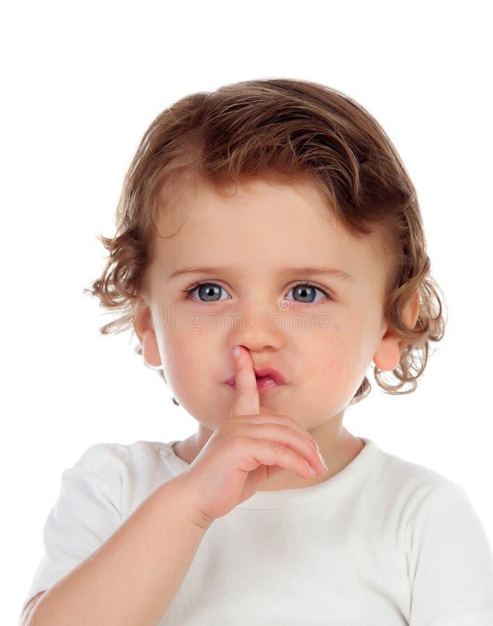 Il bambino sveglio ha messo l'indice alle labbra come segno di silenzio fotografia stock