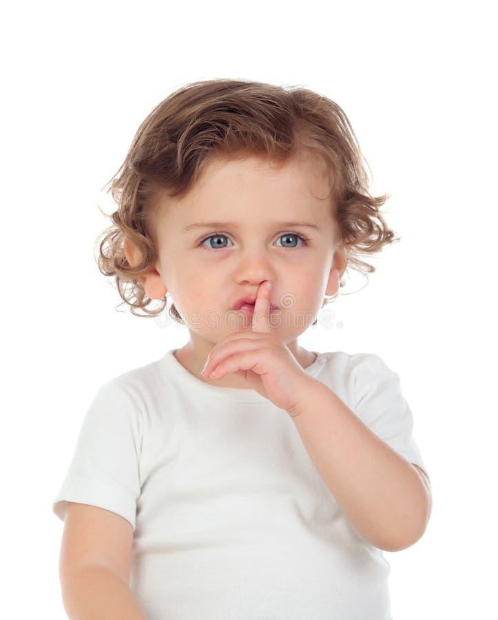 Il bambino sveglio ha messo l'indice alle labbra come segno di silenzio fotografia stock libera da diritti