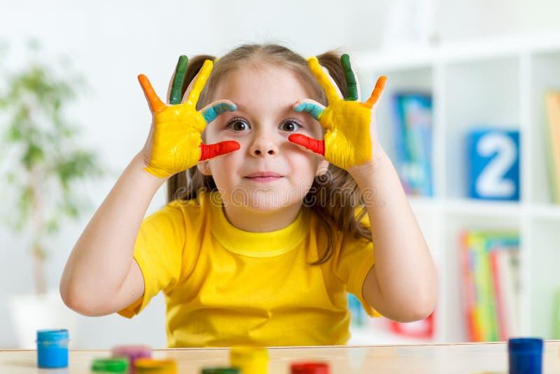 Il bambino sveglio si diverte dipingendo le sue mani immagine stock