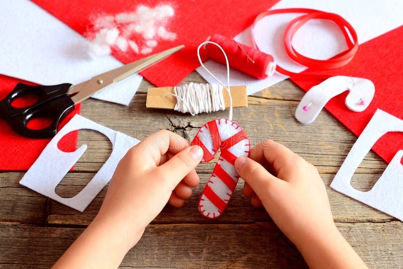 Il bambino tiene il bastoncino di zucchero del feltro di Natale in sue mani Materiali e strumenti per creare le decorazioni dell' immagini stock