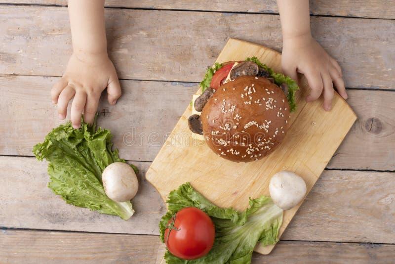 Il bambino tiene l'hamburger del fungo sopra il tagliere sulla tavola di legno immagine stock