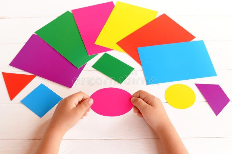 Il bambino tiene l'ovale rosa del cartone nelle mani Il bambino impara i colori e le forme geometriche Abilità di sviluppo in bam immagine stock libera da diritti