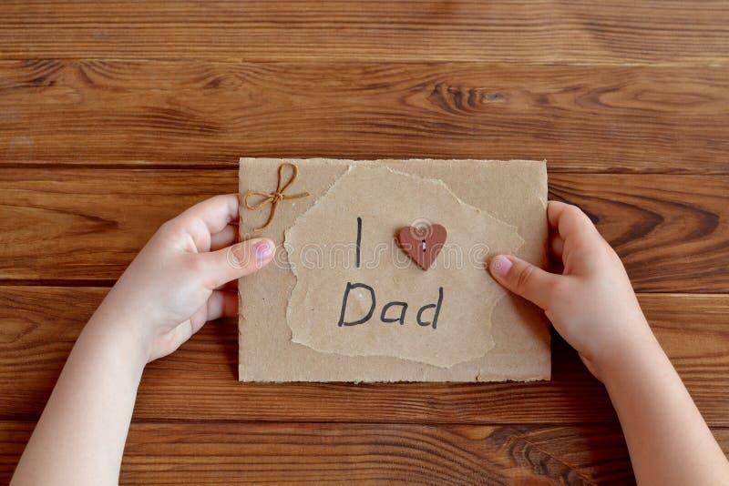 Il bambino tiene un biglietto di auguri per il compleanno per il papà immagini stock