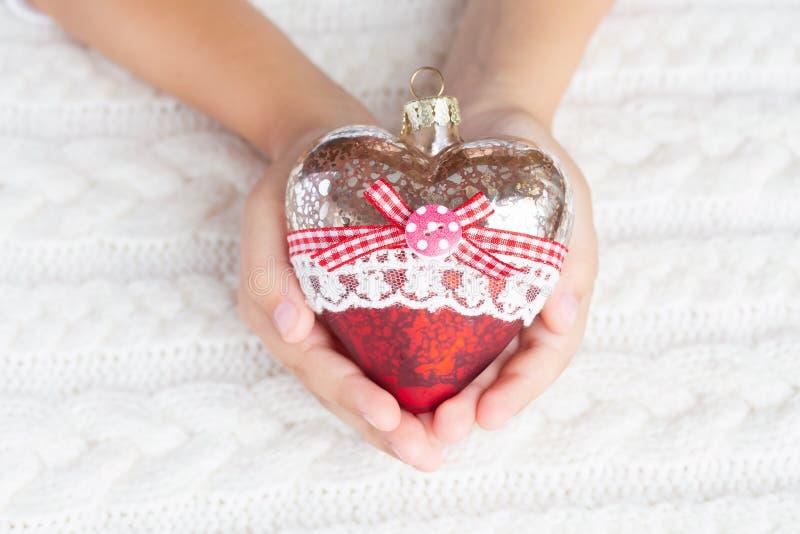 Il bambino tiene un cuore di vetro, Natale gioca nelle mani sui precedenti di un maglione tricottato caldo fotografie stock libere da diritti