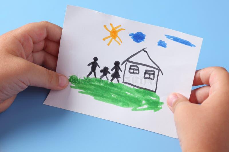 Il bambino tiene una casa tirata con la famiglia fotografia stock