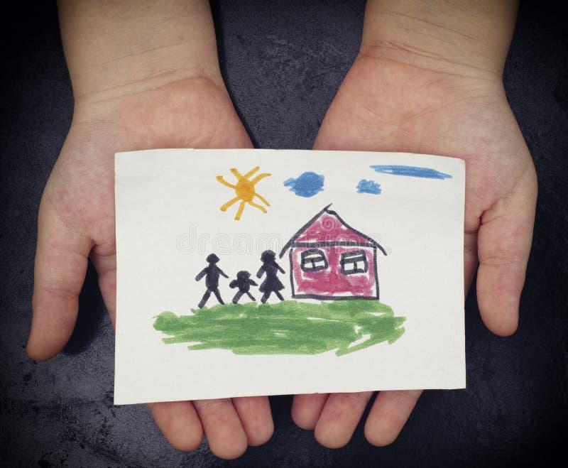 Il bambino tiene una casa tirata con la famiglia fotografia stock libera da diritti