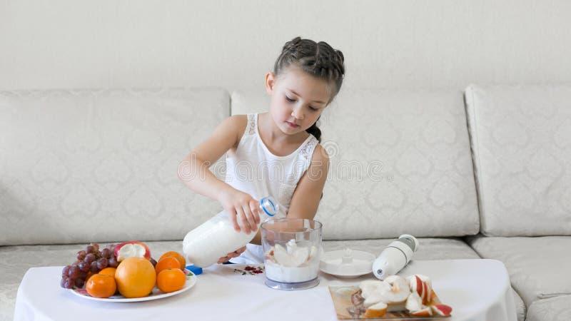 Il bambino versa il latte in un miscelatore fotografie stock libere da diritti