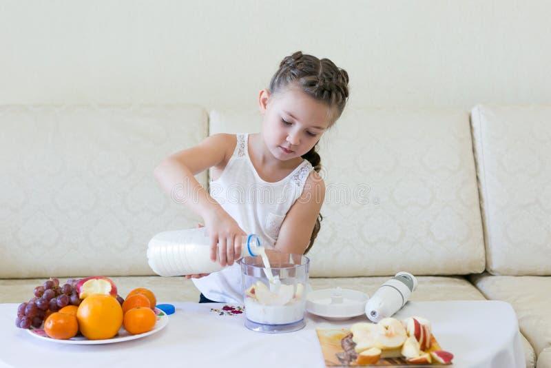 Il bambino versa il latte in un miscelatore fotografia stock