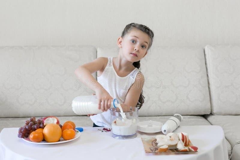 Il bambino versa il latte in un miscelatore fotografia stock libera da diritti