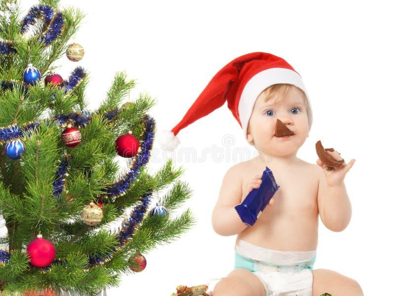 Il bambino vicino all'albero di Natale mangia l'uovo di cioccolato fotografia stock