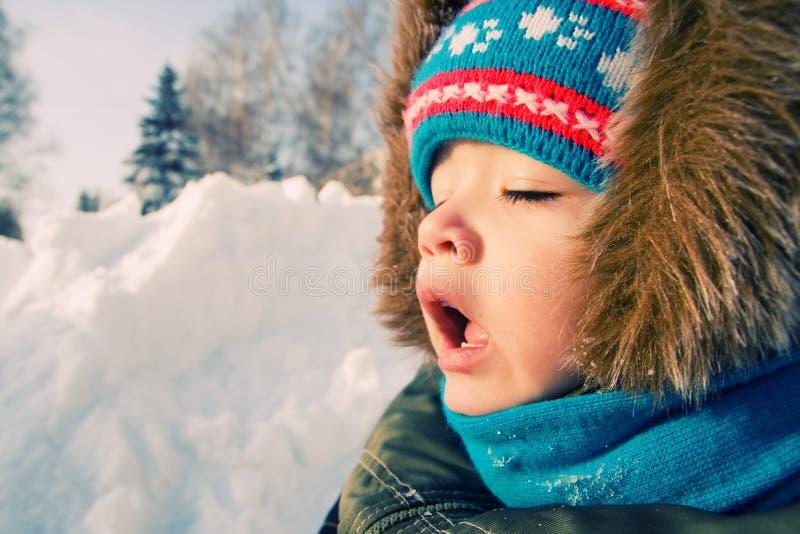 Il bambino vuole starnutire. Inverno della neve. fotografia stock