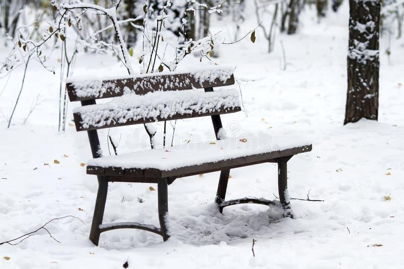 Il banco di legno vuoto in parco nell'inverno è coperto di neve immagini stock