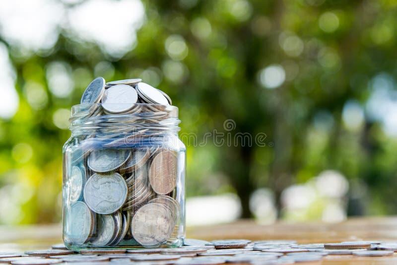 Il barattolo dei soldi ha riempito di monete su bokeh verde immagini stock