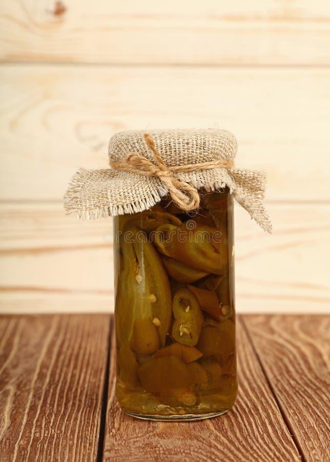 Il barattolo del jalapeno verde marinato pepa sulla tavola immagini stock