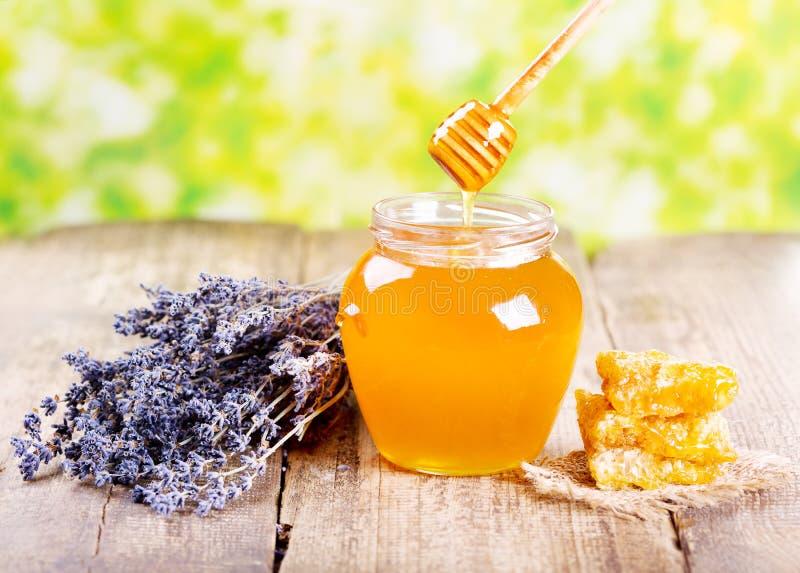 Il barattolo di miele con il favo e il lavander fiorisce fotografie stock libere da diritti