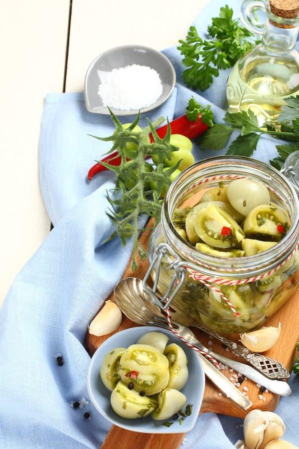 Il barattolo di vetro con i pomodori verdi marinati ha preparato per l'inverno fotografia stock libera da diritti