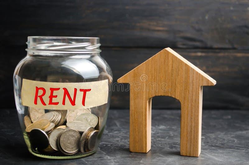 Il barattolo di vetro con le monete e il ` dell'iscrizione affittano il ` e una piccola casa di legno Affitto della proprietà, ap immagini stock libere da diritti