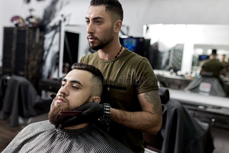 Il barbiere bello tiene le sue mani sulla barba di giovane uomo brutale e degli sguardi allo specchio ad un parrucchiere immagini stock