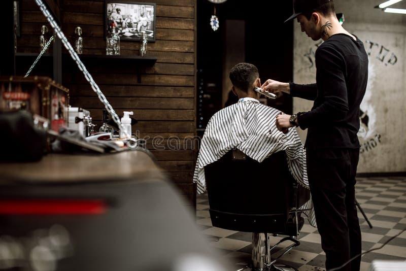 Il barbiere di modo vestito in vestiti neri fa i capelli del taglio di rasoio per un uomo moro alla moda in un alla moda immagini stock