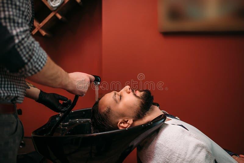 Il barbiere lava i capelli di un uomo del cliente fotografie stock