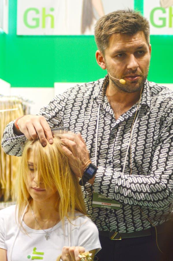 Il barbiere matrice d'avanguardia rende ad un updo alla moda i giovani capelli biondi della donna mostrare immagine stock
