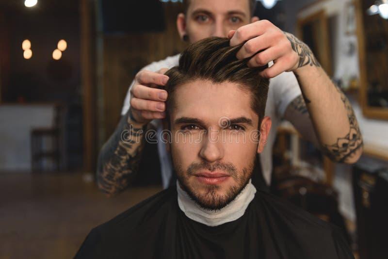 Il barbiere regola i capelli di un uomo fotografie stock
