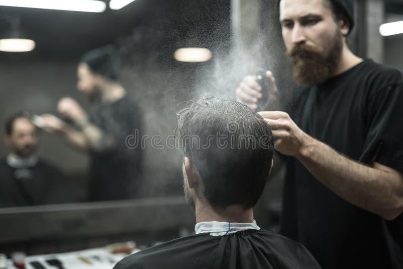 Il barbiere sta utilizzando la bottiglia dello spruzzo immagini stock libere da diritti