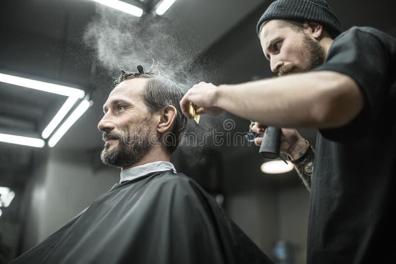 Il barbiere sta utilizzando la bottiglia dello spruzzo immagini stock