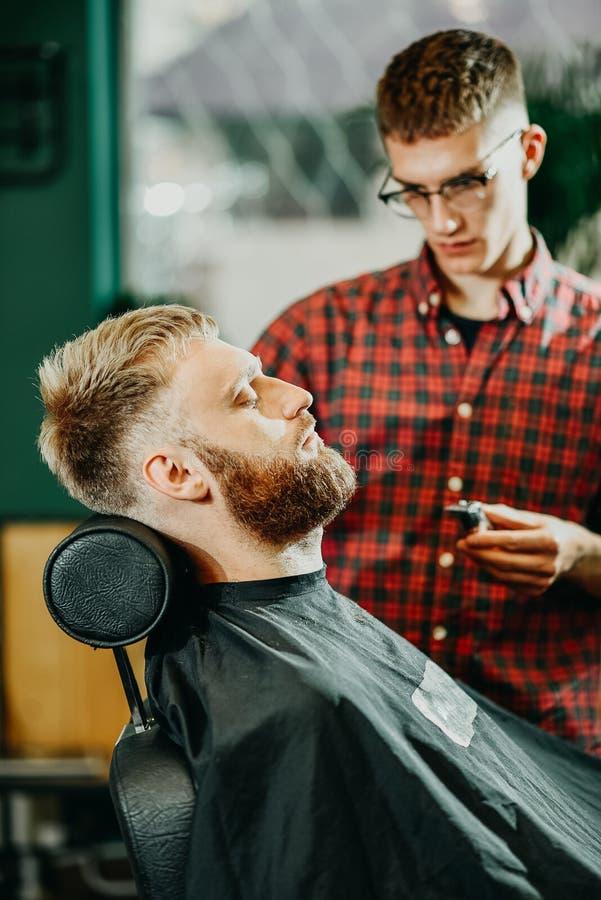 Il barbiere taglia la sua barba ad un uomo nel salone immagini stock libere da diritti
