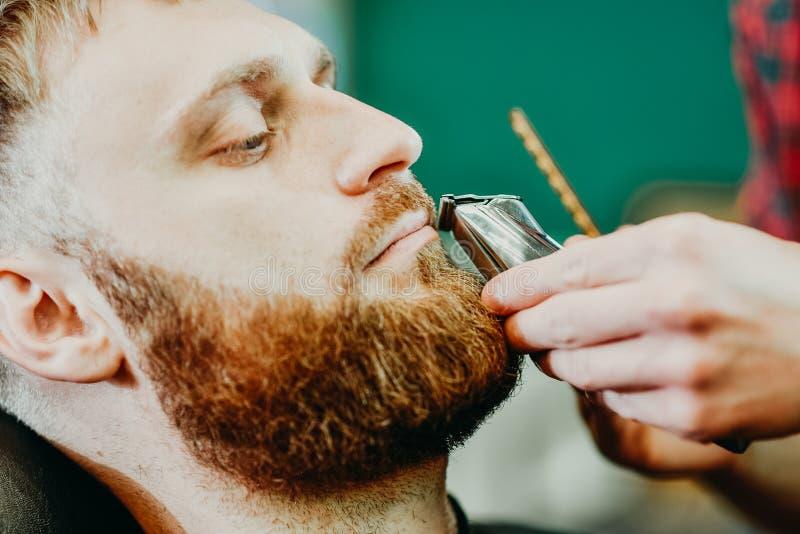 Il barbiere taglia la sua barba ad un uomo nel salone fotografia stock
