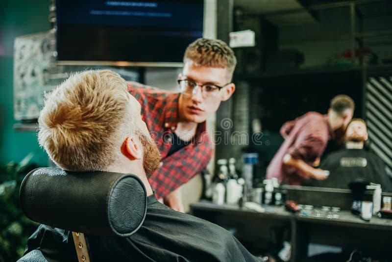 Il barbiere taglia la sua barba ad un uomo nel salone immagine stock libera da diritti