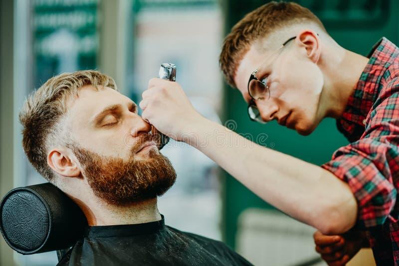 Il barbiere taglia la sua barba ad un uomo nel salone immagine stock